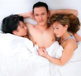Man in bed met twee vrouwen